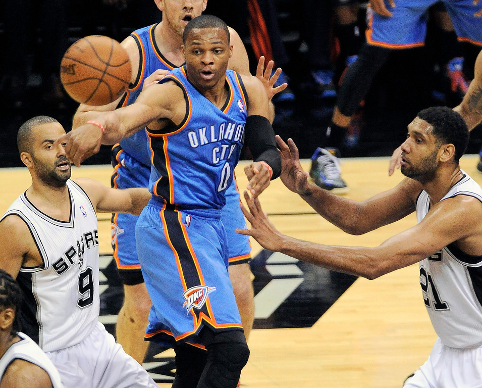 . Oklahoma City Thunder guard Russell Westbrook, center, passes between San Antonio Spurs guard Tony Parker, left, of France, and Spurs forward Tim Duncan, during the first half of an NBA playoff basketball game on Monday, May 19, 2014, in San Antonio. (AP Photo/Darren Abate)