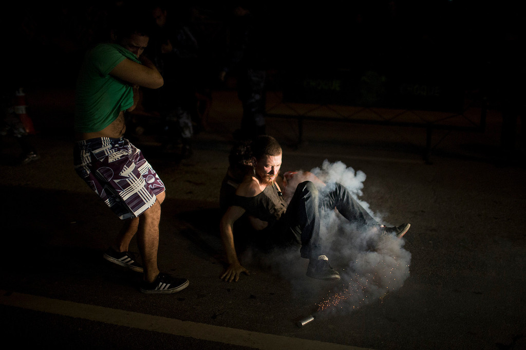 . A supporter of Indians occupying the old Indian Museum kicks a tear gas can fired by police outside the museum in Rio de Janeiro, Friday, March 22, 2013. Police in riot gear invaded an old Indian museum complex Friday and pulled out a few dozen indigenous people who for months resisted eviction from the building, which will be razed as part of World Cup preparations next to the legendary Maracana football stadium. (AP Photo/Felipe Dana)
