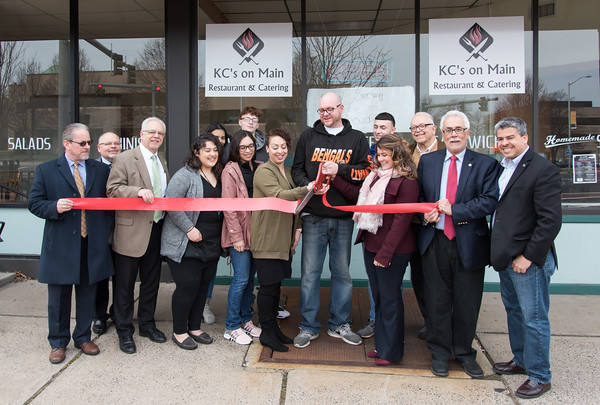 03/27/18 Wesley Bunnell | Staff Owner Keith Selander, holding scissors, of KC's on Main Restaurant & Catering held a ribbon cutting on Tuesday afternoon at his location at 2 Main St. President of the New Britain Chamber of Commerce Tim Stewart, L, holds the ribbon with Economic Development Director Bill Carroll next, Mayor Erin Stewart , R of Selander, Alderman Daniel Salerno and Carmelo Rodriguez.