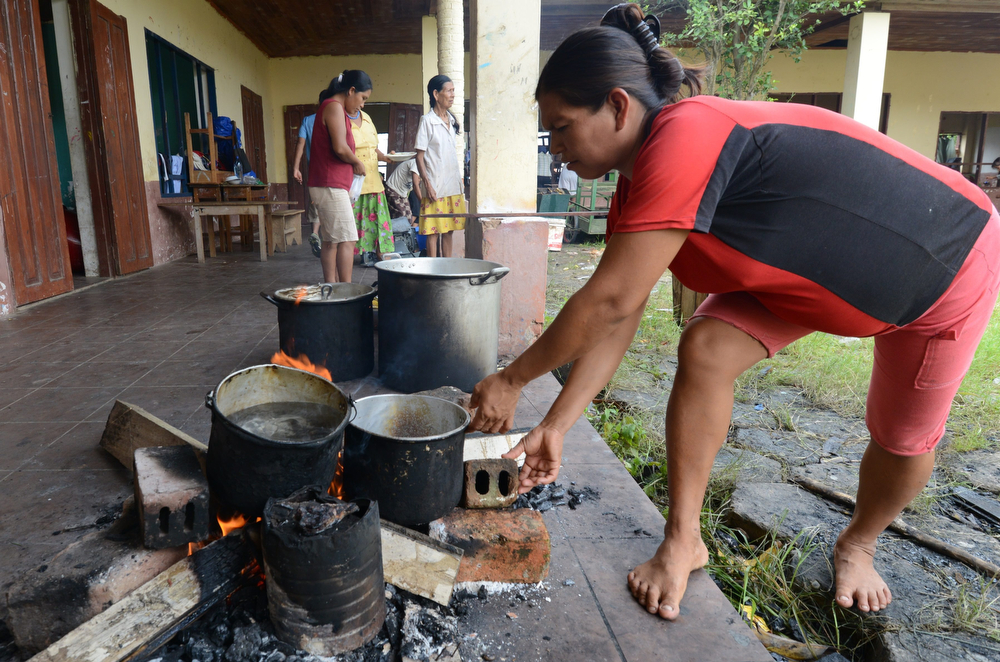 Description of . A woman cooks at a refuge in Rurrenabaque, Bolivia, on February 3, 2014, after Puerto Yumani was flooded due to the overflowing of the Beni river during heavy rains. (Aizar Raldes Nunez/AFP/Getty Images)