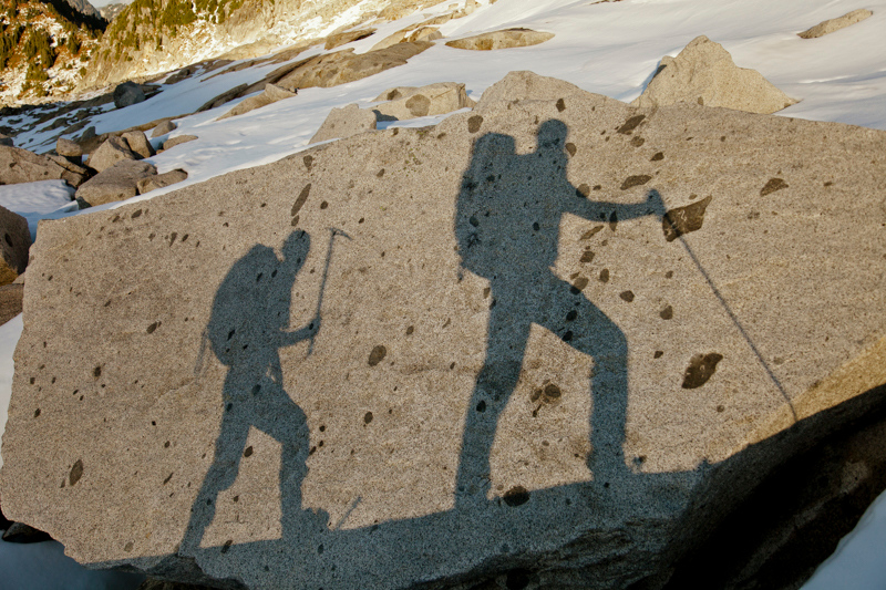 The shadows of two backpackers on a large rock.