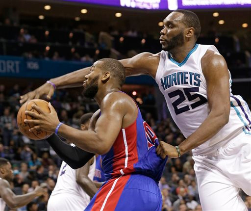 . Detroit Pistons\' Greg Monroe, left, is fouled by Charlotte Hornets\' Al Jefferson, right, during the second half of an NBA basketball game in Charlotte, N.C., Tuesday, Feb. 10, 2015. The Pistons won 106-78. (AP Photo/Chuck Burton)