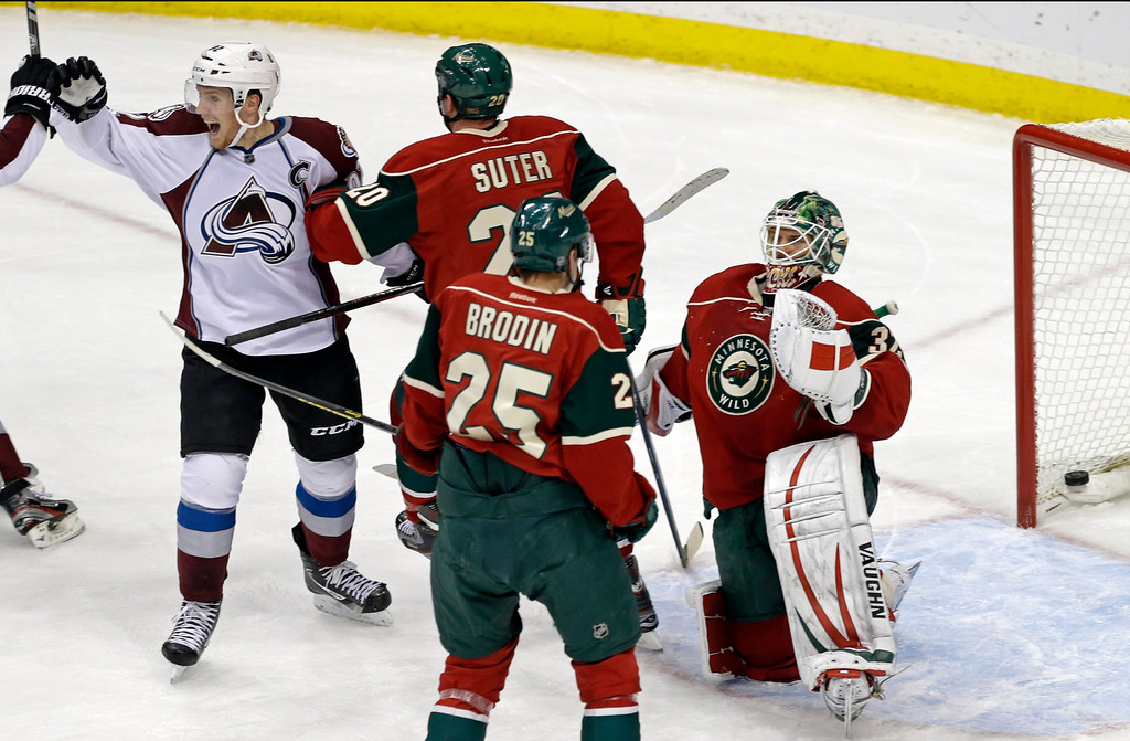. Colorado Avalanche\'s Gabriel Landeskog, left, of Sweden, celebrates after a power-play goal by P.A. Parenteau against Minnesota Wild goalie Niklas Backstrom, right, of Finland, during the first period of an NHL hockey game Thursday, March 14, 2013, in St. Paul, Minn. (AP Photo/Jim Mone)