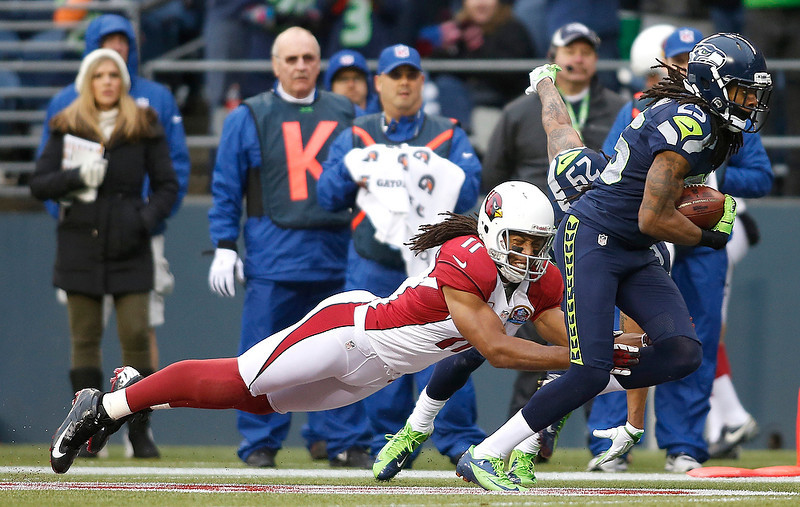 . Seattle Seahawks cornerback Richard Sherman (25) runs past Arizona Cardinals wide receiver Larry Fitzgerald (11) as he returns an interception for a 19-yard touchdown during the second quarter of an NFL football game in Seattle, Sunday, Dec. 9, 2012. (AP Photo/John Froschauer)