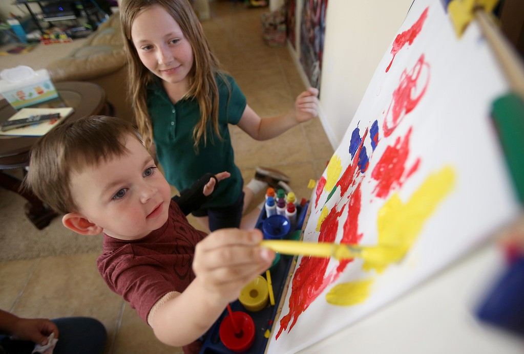. Matthew Ouimet, 3, paints a picture at their home in Antioch, Calif., on Thursday, May 22, 2014. To the right is his sister Molly, 11, who has a less serious form of the disease. (Jane Tyska/Bay Area News Group)