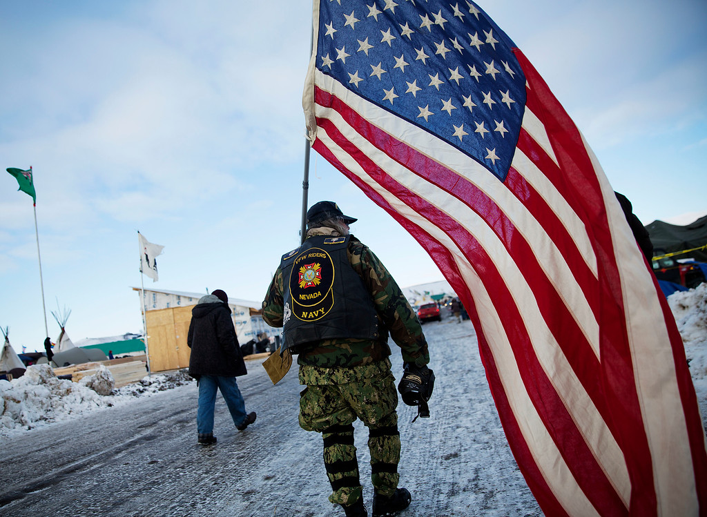 . Navy veteran Rob McHaney, of Reno, N.V., walks with an American flag at the Oceti Sakowin camp where people have gathered to protest the Dakota Access oil pipeline in Cannon Ball, N.D., Sunday, Dec. 4, 2016. Tribal elders have asked the military veterans joining the large Dakota Access pipeline protest encampment not to have confrontations with law enforcement officials, an organizer with Veterans Stand for Standing Rock said Sunday, adding the group is there to help out those who\'ve dug in against the four-state, $3.8 billion project. (AP Photo/David Goldman)