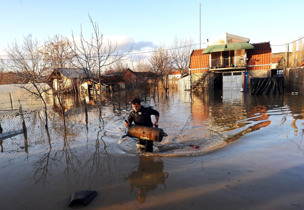 Description of . A man carries his belongings from his flooded home in the town of Sveti Nikole, some 60 kilometers northeast from Skopje on February 26, 2013. Torrential rains in the last three days caused dozens of floods, affecting many villages and towns, and damaging crops. ROBERT ATANASOVSKI/AFP/Getty Images