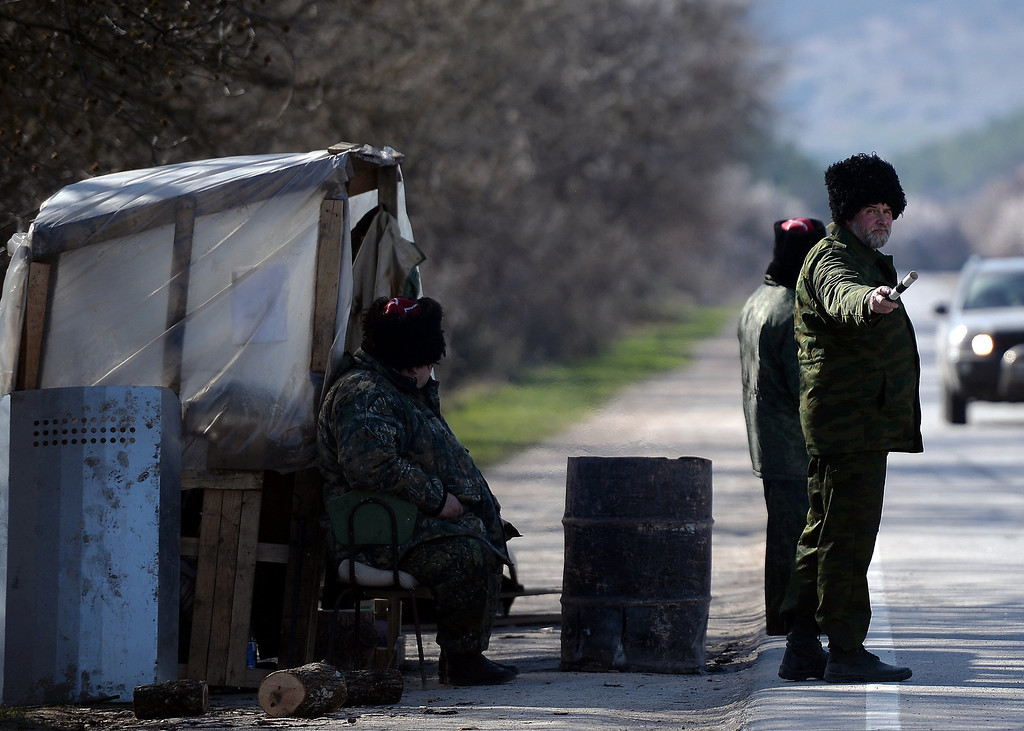 . Cossack armed men working with Pro-Russian forces stand guard at a check point on the road from Simferopol to Sevastopol on March 13, 2014. Several Serbian war veterans identifying themselves as Chetniks have joined pro-Russian troops in Ukraine\'s Crimea region. Less than three weeks after gunmen seized Crimea\'s parliament and installed a pro-Moscow government, voters here head to the polls on March 16 for a vote set to cement Russia\'s takeover of the strategic peninsula. FILIPPO MONTEFORTE/AFP/Getty Images