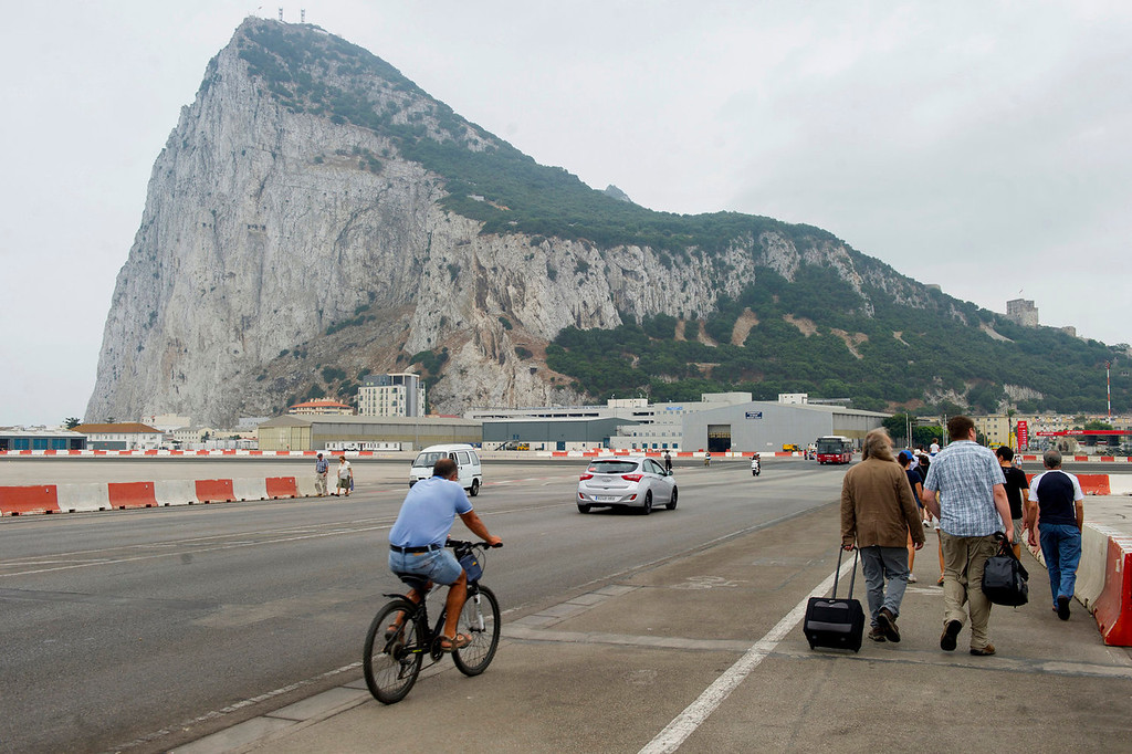 . People cross the Gibraltar airport tarmac after the border crossing between Spain and Gibraltar on August 13, 2013. Irate drivers waited up to five hours to enter Gibraltar today, some even pushing their cars to save fuel, as Spain enforced tight border checks in a growing row with Britain over the tiny territory and its surrounding waters. The latest flare-up was sparked when Gibraltar sank concrete blocks in disputed waters to create an artificial reef, making it impossible for Spanish fishing fleets to operate in the area.   MARCOS MORENO/AFP/Getty Images