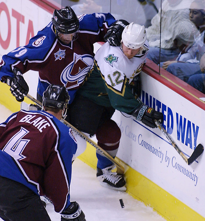. Colorado Avalanche left winger Ville Nieminen (39) fights for the puck with Dallas Stars left winger Mike Keane (12) as Rob Blake (4) looks on during the first period in Denver, Sunday, March 11, 2001. (AP Photo/Jack Dempsey)
