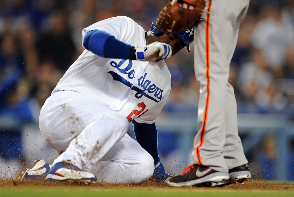 . Los Angeles Dodgers\' Carl Crawford scores on a passed ball in the first inning of their baseball game against the San Francisco Giants on Wednesday, April 3, 2013 in Los Angeles. 