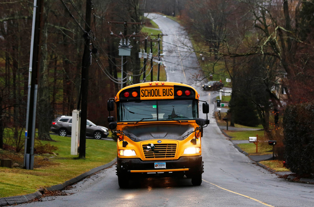 Description of . A school bus carrying students from the Newtown school district makes its way down a street in Newtown, Connecticut December 18, 2012. The schools of Newtown, which stood empty in the wake of a shooting rampage that took 26 of their own at Sandy Hook Elementary, will again ring with the sounds of students and teachers on Tuesday as the bucolic Connecticut town struggles to return to normal. REUTERS/Shannon Stapleton