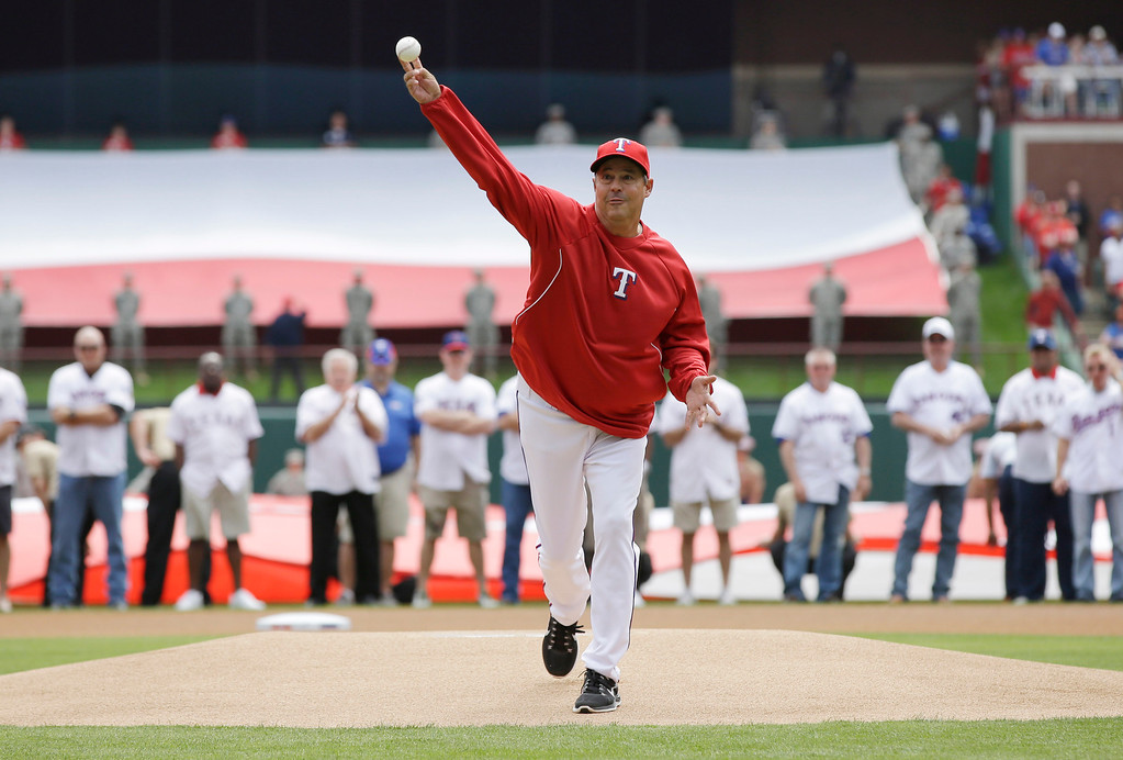 . The ceremonial first pitch is thrown by former professional baseball player and four-time Cy Young Award winner Greg Maddux before an on opening day baseball game against the Philadelphia Phillies at Globe Life Park, Monday, March 31, 2014, in Arlington, Texas. (AP Photo/Tony Gutierrez)