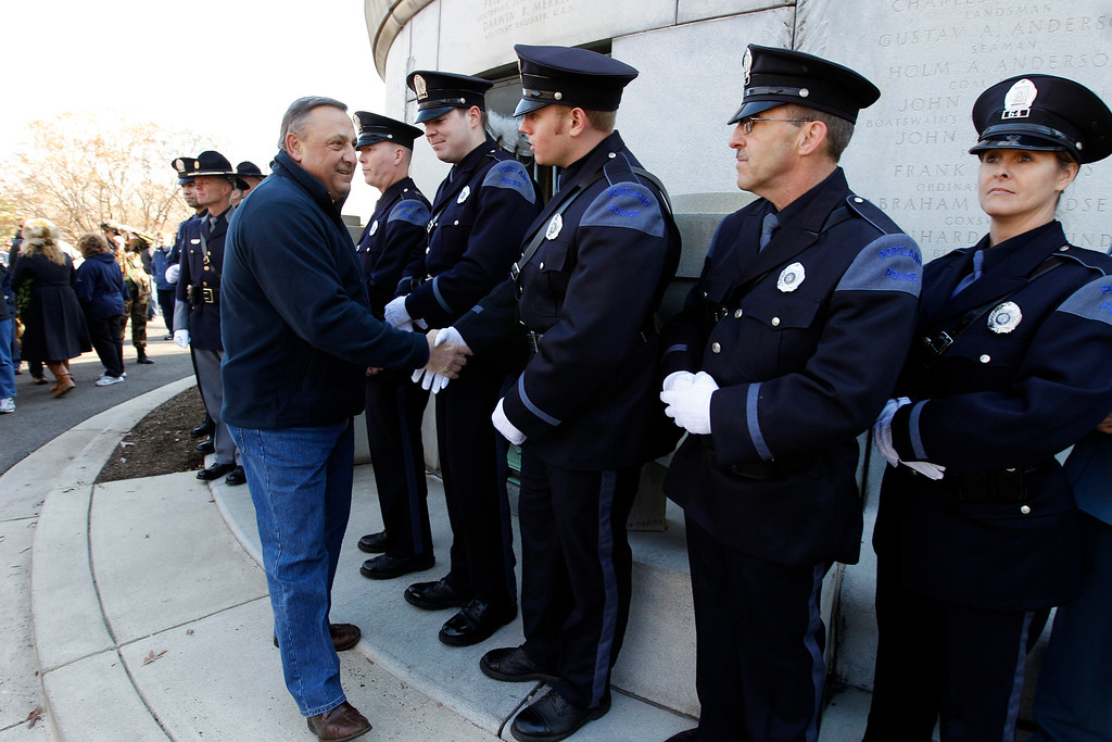 . Maine Gov. Paul LePage shake hands with Portland, Maine, police officers during the ceremony at USS Maine Mast during holiday wreaths laying at graves at Arlington National Cemetery in Arlington, Va. on Saturday, Dec. 15, 2012, during Wreaths Across America Day. Wreaths Across America was started in 1992 at Arlington National Cemetery by Maine businessman Morrill Worcester and has expanded to hundreds of veterans\' cemeteries and other locations in all 50 states and beyond.  (AP Photo/Jose Luis Magana)