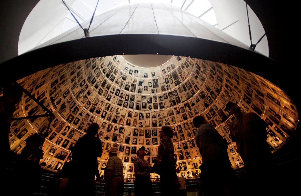 Description of . Visitors look at pictures of Jews killed in the Holocaust in the Hall of Names in the Yad Vashem Holocaust Memorial in Jerusalem on Sunday, April 7, 2013. The annual Israeli memorial day for the 6 million Jews killed in the Holocaust of World War II begins at sundown Sunday. (AP Photo/Sebastian Scheiner)