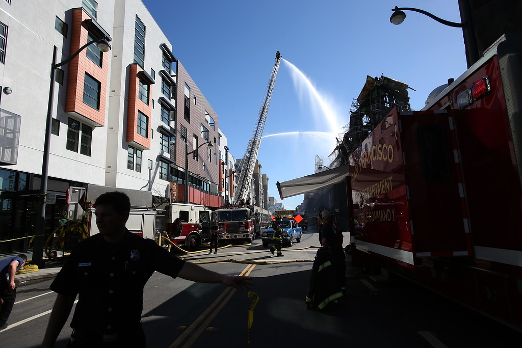. Firefighters hose down hot spots as crews begin demolition of an apartment complex on Fourth Street in the Mission Bay neighborhood of San Francisco, Calif., on Wednesday, March 12, 2014. Firefighters remained on scene as the remains of the $227 million project were still smoldering after being destroyed by a massive 5-alarm blaze on Tuesday. (Jane Tyska/Bay Area News Group)