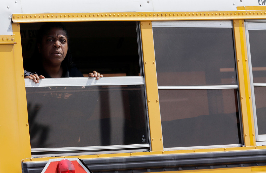 . A woman looks out a school bus as it leaves Spring High School Wednesday, Sept. 4, 2013, in Spring, Texas.  (AP Photo/David J. Phillip)