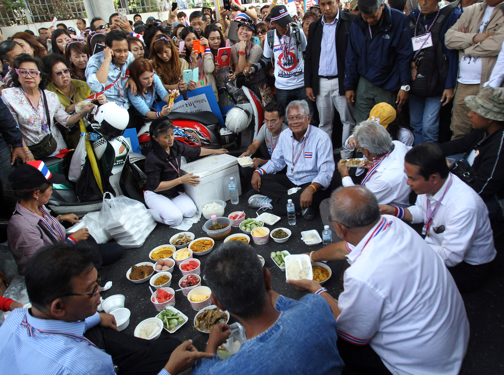 . Anti-government protest leader Suthep Thaugsuban, center, sits with others for lunch during a protest rally, Tuesday, Jan. 21, 2014, in Bangkok, Thailand. Twin explosions shook an anti-government demonstration site in Thailand\'s capital, wounding dozens of people in the latest violence to hit Bangkok as the nation\'s increasingly bloody political crisis drags on. (AP Photo/Sakchai Lalit)