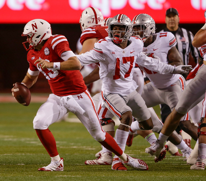 . Ohio State linebacker Jerome Baker (17) and defensive end Jalyn Holmes (11) pursue Nebraska quarterback Tanner Lee (13) during the first half of an NCAA college football game in Lincoln, Neb., Saturday, Oct. 14, 2017. (AP Photo/Nati Harnik)