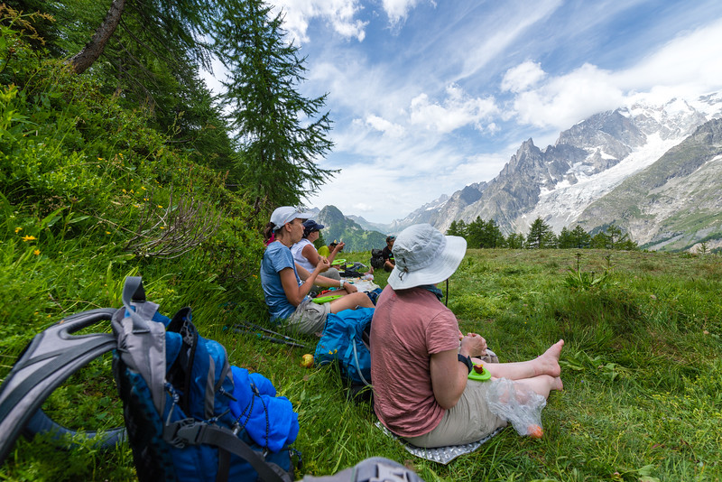 Hikers sit in the grass resting with a mountain view.