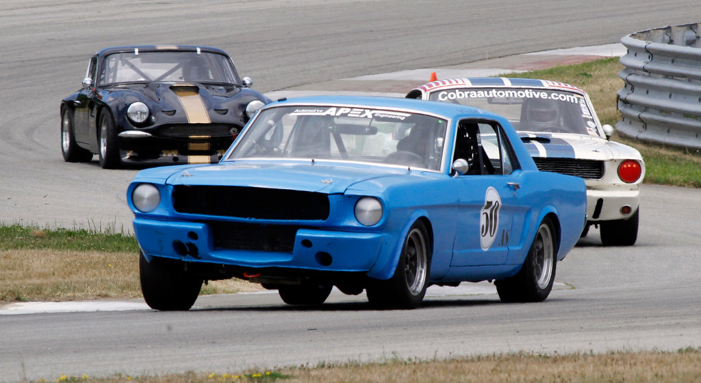 . Norman Hosselbarth of Medway, Mass., drives his 1965 Ford Mustang into the second turn ahead of a 1966 Shelby Mustang co-driven by Hal McCarty and Kevin Kommit from Marshall, Va. as the 1969 TVR Tuscan driven by Pittsburgh\'s Christopher Zappa follows as they participate at a high speed test and tune session for the Pittsburgh Vintage Grand Prix, Friday, July 15, 2011 at the BeaveRun Motorsports Complex in Wampum, Pa.   (AP Photo/Keith Srakocic)