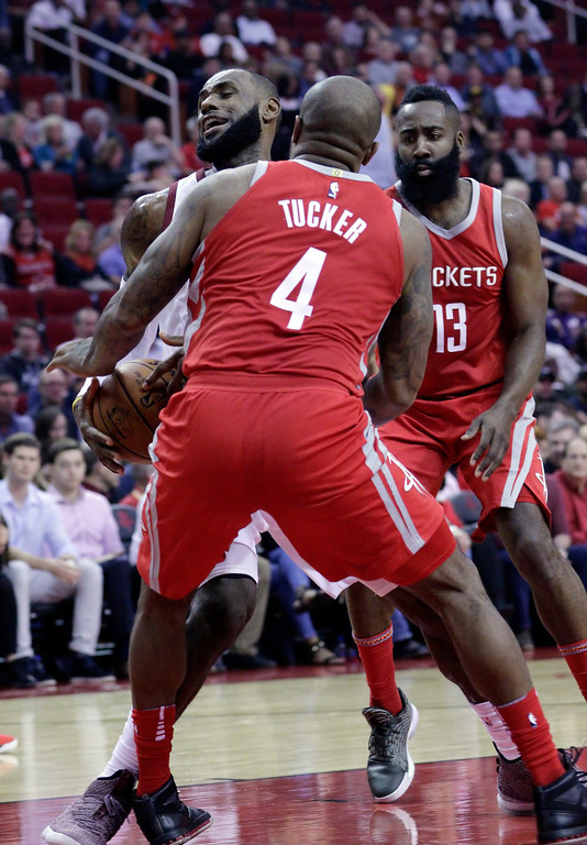 . Cleveland Cavaliers forward LeBron James (23) is boxed up by Houston Rockets forward PJ Tucker (4) and guard James Harden (13) during the first half of an NBA basketball game Thursday, Nov. 9, 2017, in Houston. (AP Photo/Michael Wyke)