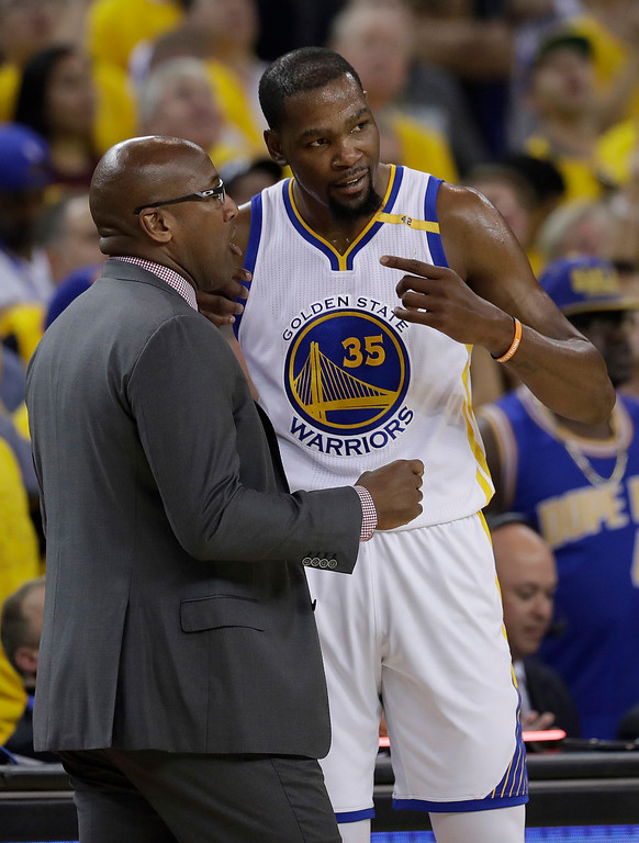 . Golden State Warriors forward Kevin Durant (35) talks with interim head coach Mike Brown during the first half of Game 1 of basketball\'s NBA Finals against the Cleveland Cavaliers in Oakland, Calif., Thursday, June 1, 2017. (AP Photo/Marcio Jose Sanchez)