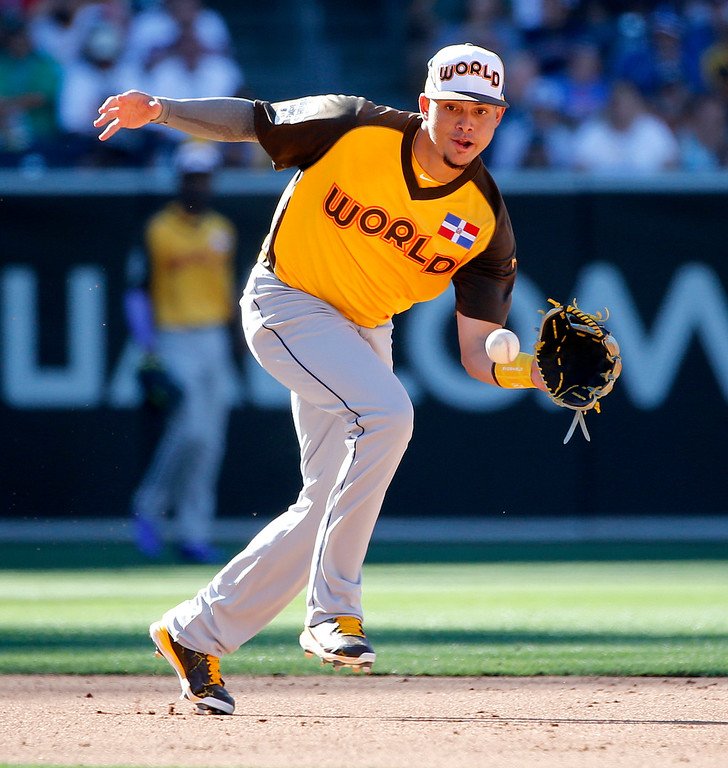 . World Team\'s Willy Adames, of the Tampa Bay Rays, fields a ball hit by U.S. Team\'s Travis Demeritte, of the Texas Rangers, during the fourth inning of the All-Star Futures baseball game, Sunday, July 10, 2016, in San Diego. (AP Photo/Lenny Ignelzi)