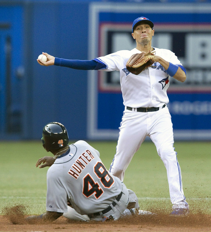 . Toronto Blue Jays\' Ryan Goins gets the force out on Detroit Tigers\' Tori Hunter at second base but fails to turn the double play during the second inning of a baseball game, Friday, Aug. 8, 2014 in Toronto. (AP Photo/The Canadian Press, Fred Thornhill)