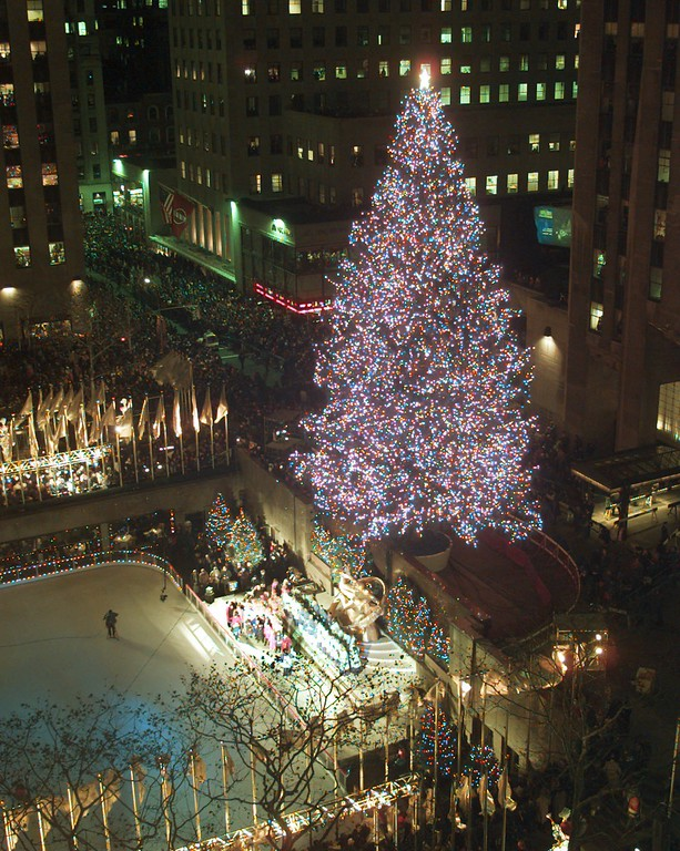 . New York\'s Rockefeller Center takes its turn in the holiday spotlight with the 64th annual lighting of the Rockefeller Center tree Tuesday, Dec. 3, 1996. The 90-foot Norway spruce was set aglow with 26,000 lights on miles of swirling wire. (AP Photo/ Mark Lennihan)