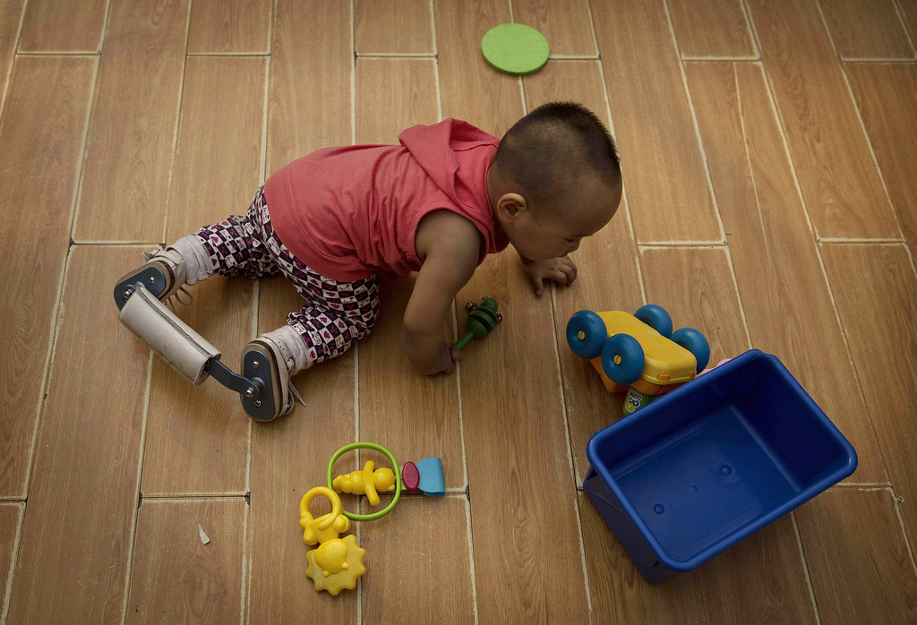 . A young Chinese orphaned boy crawls wearing corrective leg braces on the floor of a foster care center on April 2, 2014 in Beijing, China. (Photo by Kevin Frayer/Getty Images)