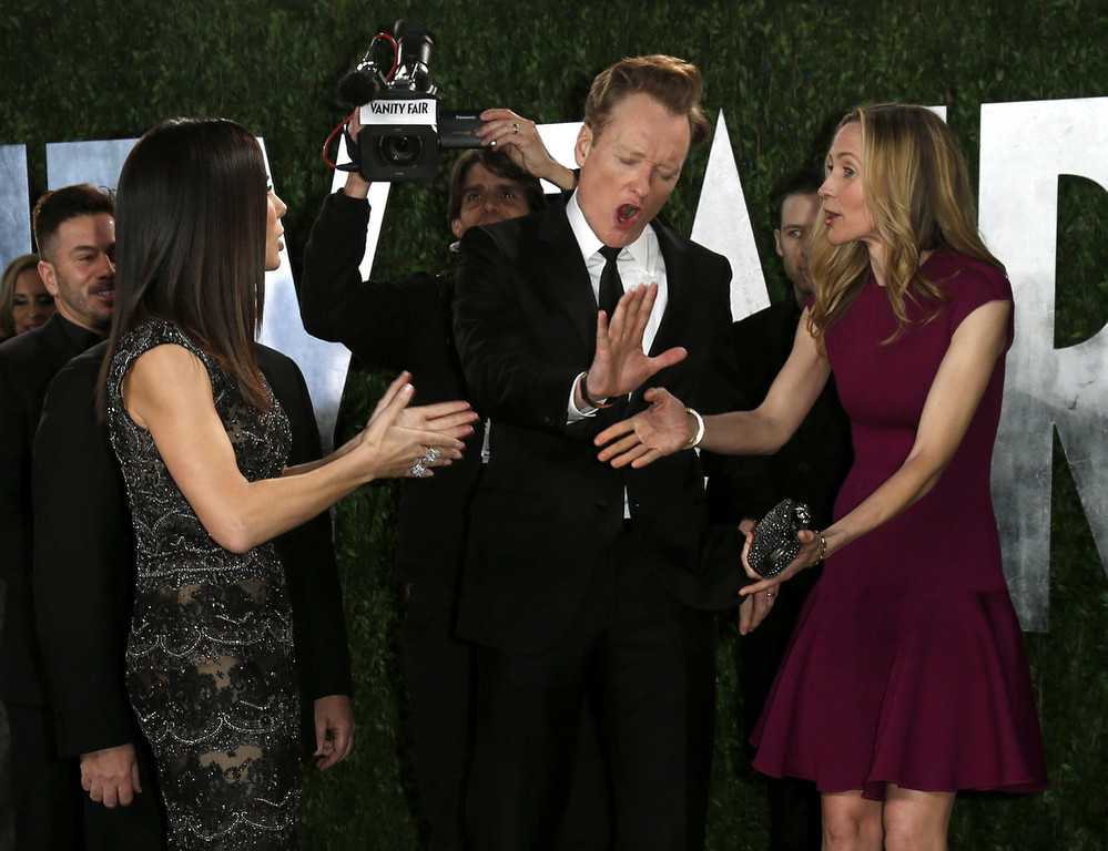 . Sandra Bullock (L), Conan O\'Brien and wife Liza Joke (R) around before posing on the carpet at the 2013 Vanity Fair Oscars Party in West Hollywood, California February 24, 2013.  REUTERS/Danny Moloshok