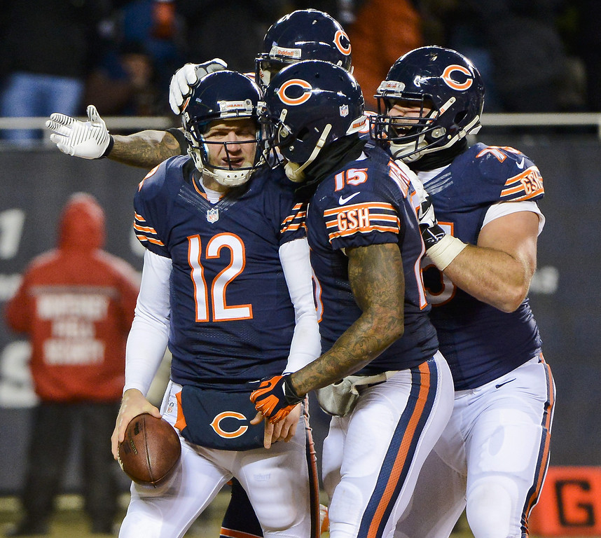 . Chicago Bears quarterback Josh McCown (L) is surrounded by teammates after scoring a touchdown against the Dallas Cowboys in the first half of their NFL game at Soldier Field in Chicago, Illinois. EPA/TANNEN MAURY