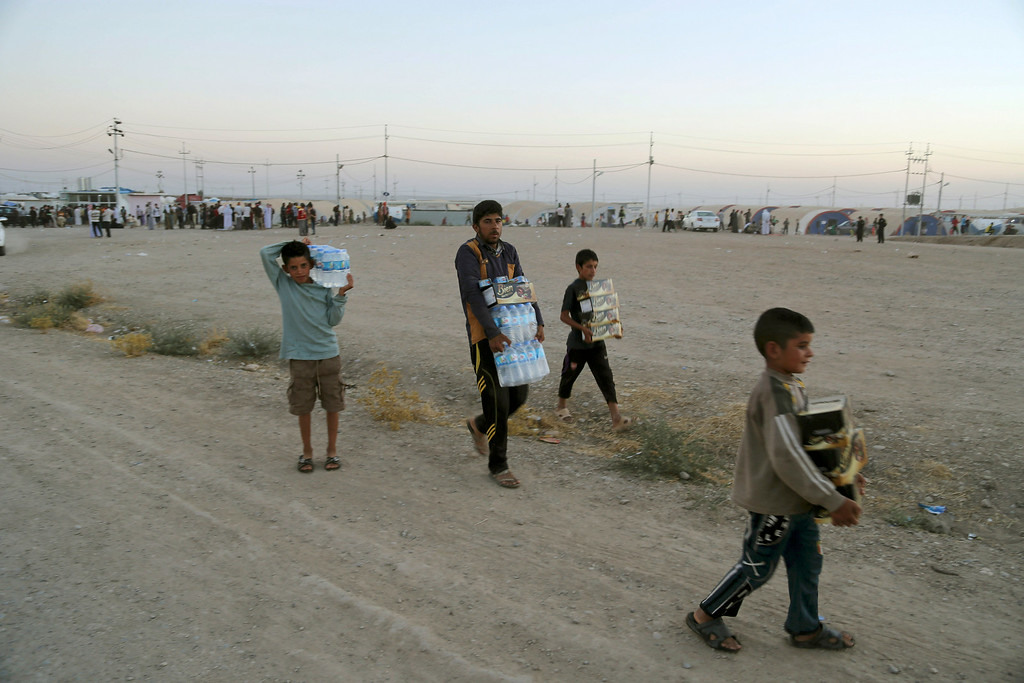 . Displaced Iraqi from the Yazidi community carry humanitarian aid at the camp of Bajid Kandala at Feeshkhabour town near the Syria-Iraq border, in Iraq Saturday, Aug. 9, 2014. (AP Photo/ Khalid Mohammed)