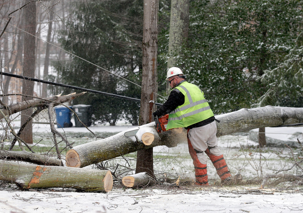 . A Duke Energy worker uses a chainsaw to cut a fallen tree from power lines in Matthews, N.C., Friday, Jan. 22, 2016. A massive blizzard began dumping snow on the southern and eastern United States on Friday, with mass flight cancellations, five states declaring states of emergency and more than 2 feet (60 centimeters) predicted for Washington alone. (AP Photo/Chuck Burton)