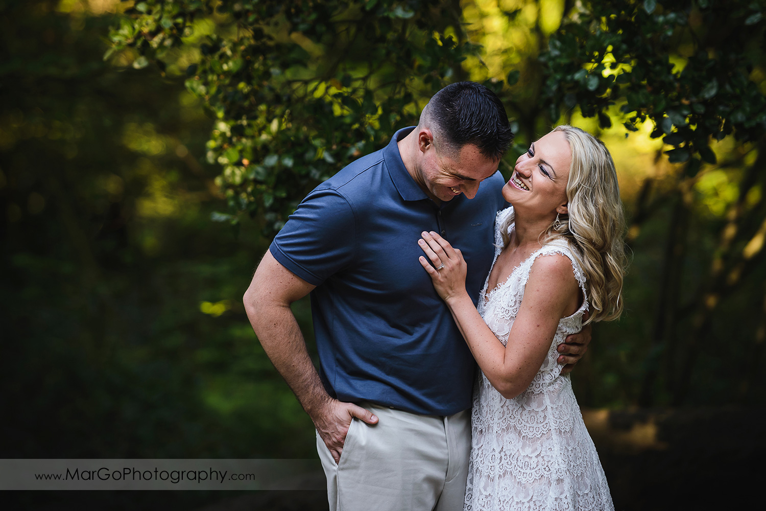 3/4 portrait of man in navy blue shirt and woman in white dress laughing during engagement session at San Francisco Golden Gate Park