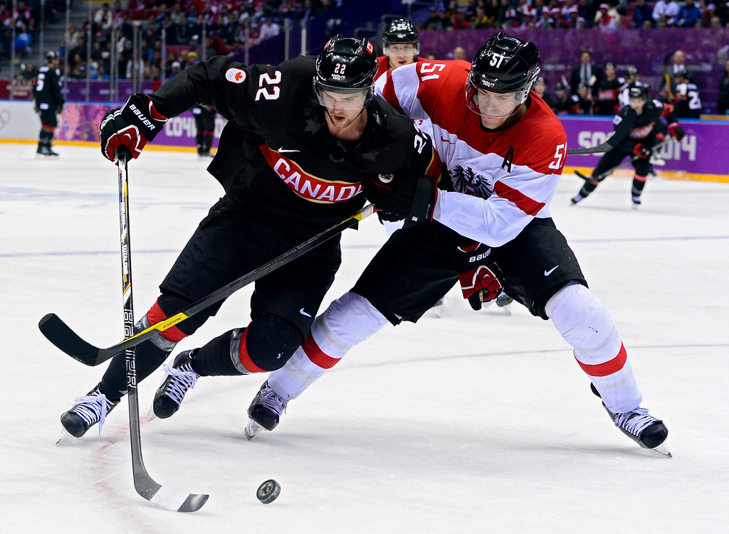. Matthias Tratting (R) of Austria fights for the puck with Jamie Benn (L) of Canada in the third period of the Men\'s Preliminary Round Group B match between Canada and Austria at the Bolshoy Ice Dome in the Ice Hockey tournament at the Sochi 2014 Olympic Games in Sochi, Russia, 14 February 2014. Canada won the match 6-0.  EPA/LARRY W. SMITH