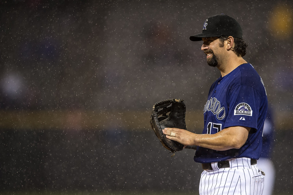 . Todd Helton #17 of the Colorado Rockies rubs his glove in the rain during a game against the San Diego Padres at Coors Field on August 12, 2013 in Denver, Colorado. A rain delay was called in the eighth inning with the Rockies leading 8-1.  (Photo by Dustin Bradford/Getty Images)