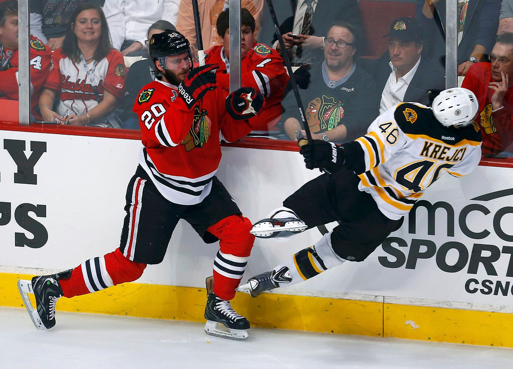 . Chicago Blackhawks\' Brandon Saad (L) checks Boston Bruins\' David Krejci during the first period in Game 1 of their NHL Stanley Cup Finals hockey series in Chicago, Illinois, June 12, 2013. REUTERS/Jeff Haynes