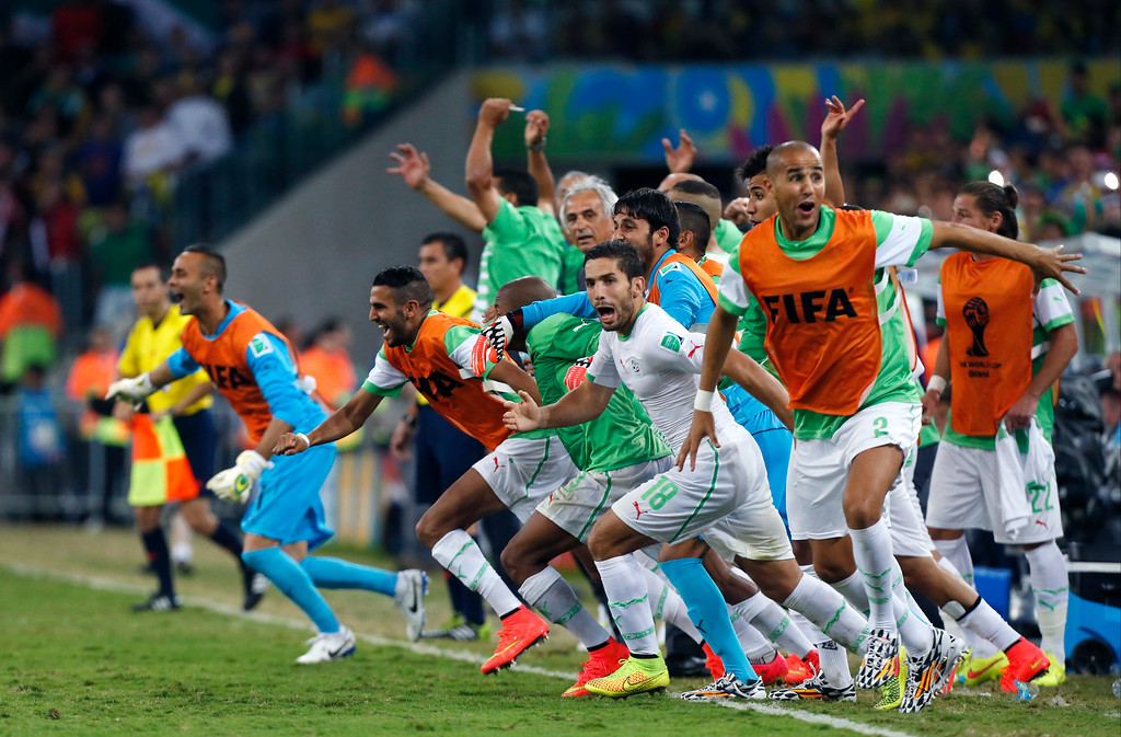 . Algeria\'s bench players run onto the pitch as they celebrate after the group H World Cup soccer match between Algeria and Russia at the Arena da Baixada in Curitiba, Brazil, Thursday, June 26, 2014. With Algeria and Russia playing to a 1-1 draw, Algeria qualified for the knock-out stage. (AP Photo/Jon Super)