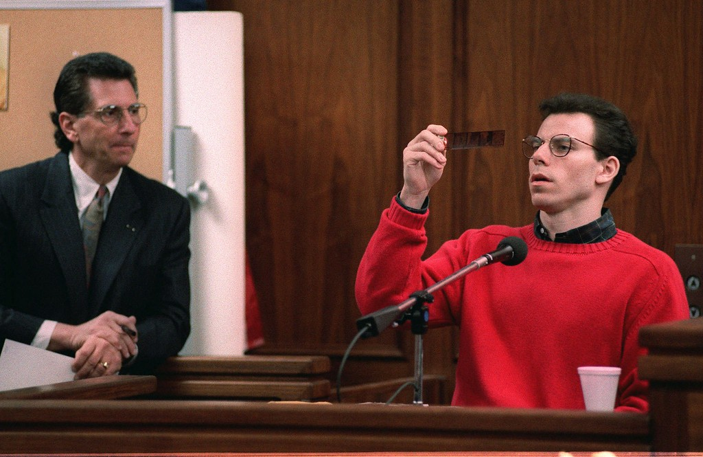 . Defense attorney Barry Levin watches as Erik Menendez looks at negatives of photos taken by his father when Erik was 6 years old, including his 6th birthday party and nude photos of Erik, during testimony in the double-murder trial of Erik and his brother Lyle Menendez Thursday, Dec. 7, 1995, in Van Nuys Superior Court in Los Angeles.  (AP Photo/Reed Saxon)