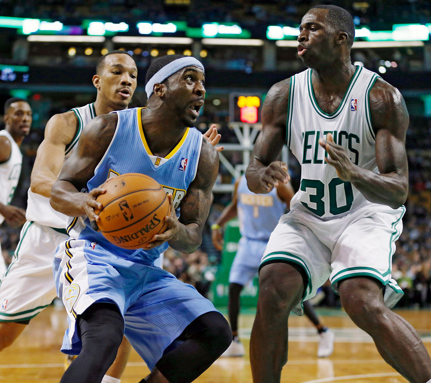 . Denver Nuggets\' Ty Lawson, center, drives for the basket as Boston Celtics\' Brandon Bass (30) defends in the second quarter of an NBA basketball game in Boston, Friday, Dec. 6, 2013. (AP Photo/Michael Dwyer)