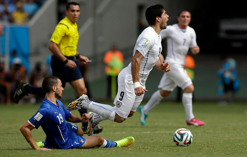 . Italy\'s Leonardo Bonucci, left, tackles Uruguay\'s Luis Suarez during the group D World Cup soccer match between Italy and Uruguay at the Arena das Dunas in Natal, Brazil, Tuesday, June 24, 2014. (AP Photo/Andrew Medichini)