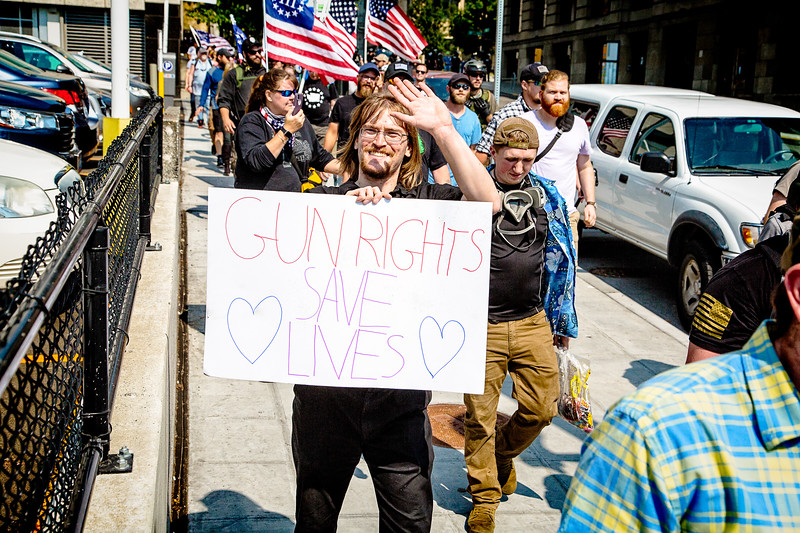 """A right wing supporter waves at me while holding his """"GUN RIGHTS SAVE LIVES"""" poster."""