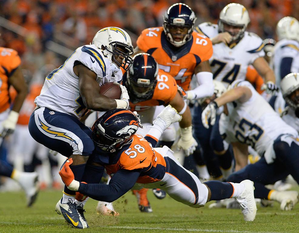 . DENVER, CO - OCTOBER 23: Branden Oliver (43) of the San Diego Chargers is stopped by Von Miller (58) of the Denver Broncos in the first quarter. The Denver Broncos played the San Diego Chargers at Sports Authority Field at Mile High in Denver on October 23, 2014. (Photo by AAron Ontiveroz/The Denver Post)