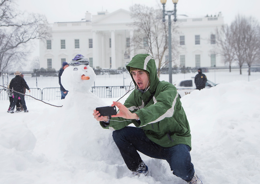 . Harrison Feind of Boulder, Colo., takes a selfie with a snowman in front of the White House in Washington, Saturday, Jan. 23, 2016. A blizzard with hurricane-force winds brought much of the East Coast to a standstill Saturday, dumping as much as 3 feet of snow, stranding tens of thousands of travelers and shutting down the nation\'s capital and its largest city. (AP Photo/Manuel Balce Ceneta)