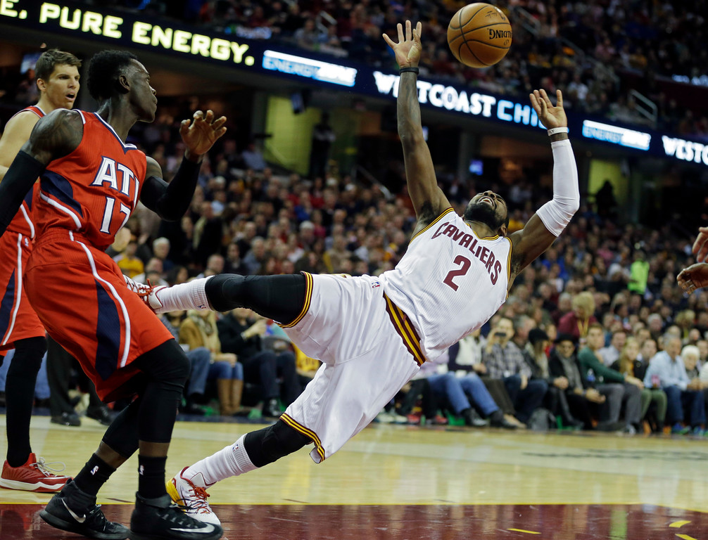 . Cleveland Cavaliers\' Kyrie Irving (2) loses the ball after being fouled by Atlanta Hawks\' Dennis Schroder, from Germany, in the first quarter of an NBA basketball game Saturday, Nov. 15, 2014, in Cleveland. (AP Photo/Mark Duncan)