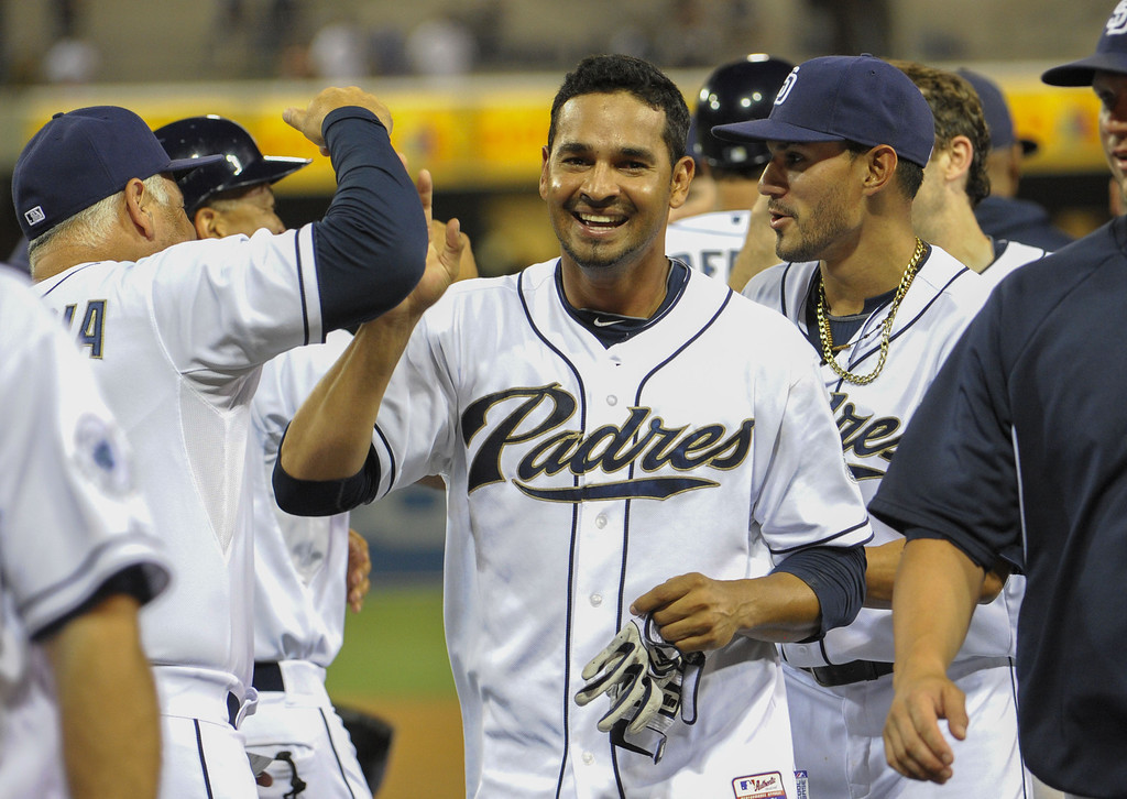 . SAN DIEGO, CA - SEPTEMBER 6:  Jesus Guzman #15 of the San Diego Padres, center, is congratulated by teammates after he hit a walk-off single during the ninth inning of a baseball game against the Colorado Rockies at Petco Park on September 6, 2013 in San Diego, California.  The Padres won 4-3. (Photo by Denis Poroy/Getty Images)