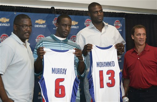 . Joe Dumars, left, Detroit Pistons president of basketball operations, and head coach Flip Saunders, right, stand with Nazr Mohammed and Flip Murray at the Palace in Auburn Hills, Mich., Tuesday, July 18, 2006. The two players signed Tuesday, adding depth to a team that has been depleted by the loss of All-Star center Ben Wallace. (AP Photo/Carlos Osorio)