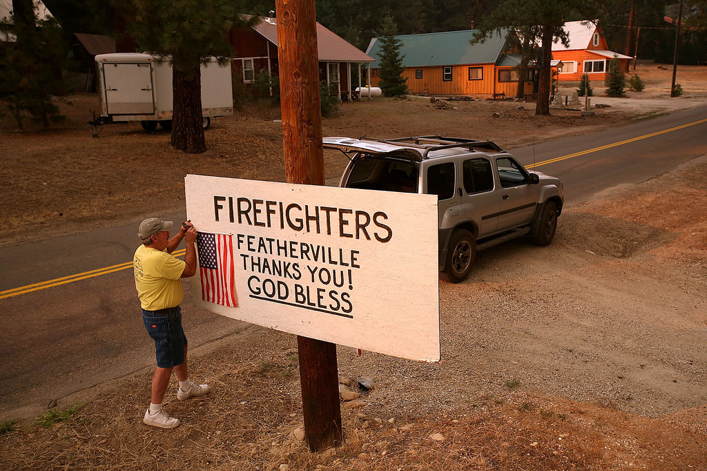 . John Lewis, of Featherville, Idaho, works on a sign as firefighters work in the area battling the Elk Fire Complex on Wednesday, Aug. 14, 2013. (AP Photo/Times-News, Ashley Smith)